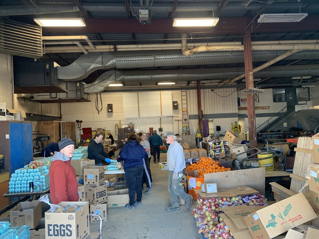 School staff volunteering to box up food